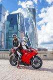 One guy and sexy girl in a suit with a motorcycle sport bike Royalty Free Stock Images