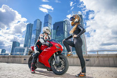 One guy and girl in a suit with a motorcycle sport bike Royalty Free Stock Photo