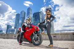 One guy and sexy girl in a suit with a motorcycle sport bike Stock Images