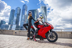 One guy and sexy girl in a suit with a motorcycle sport bike Stock Photos