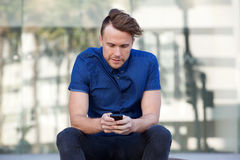 One guy sitting outside in city with mobile phone Stock Photography