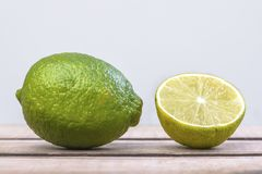 One and a half green lime. One and a half lime on a wooden table, with a grey background royalty free stock images