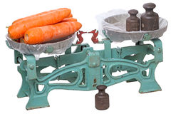 One and a half kilos carrots. The old mechanical scales with a large carrots isolated on white background stock images