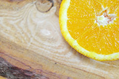 One half of an orange close up. On a plank Stock Image