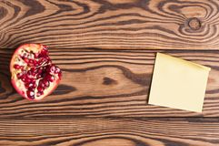 One half of red ripe fresh pomegranate and single blank yellow square paper sticky sticker on old brown weathered rustic planks. Top view royalty free stock photography