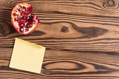 One half of red ripe fresh pomegranate and single blank yellow square paper sticky sticker. On old brown weathered rustic planks. Top view stock photo