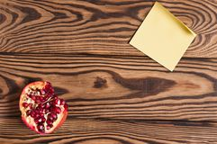 One half of red ripe fresh pomegranate and single blank yellow square paper sticky sticker. On old brown weathered rustic planks. Top view stock images