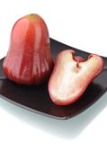 One and a half of red rose apple on black plate Royalty Free Stock Photo