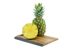 One and half ripe pineapple on the wooden board royalty free stock photo