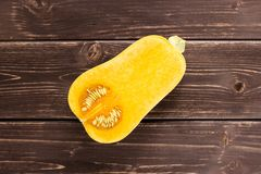 Smooth pear shaped orange butternut squash waltham on brown wood. One half of smooth pear shaped orange butternut squash waltham variety flatlay on brown wood stock photos