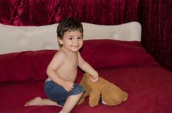 One and a half year old baby boy posing with teddy bear. On the bed, red background stock images