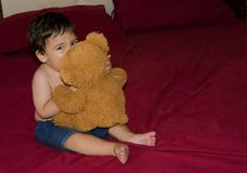 One and a half year old baby boy posing with teddy bear. On the bed, red background royalty free stock images