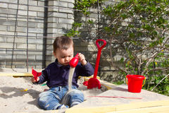 One and half year old boy is playing in sandbox Stock Photo