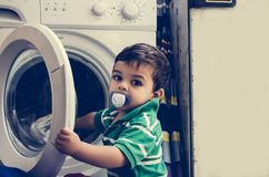 One and the half years old baby boy putting clothes in washing machine. One and the half years old baby boy helping his mom by putting clothes in washing machine royalty free stock photos