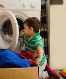 One and the half years old baby boy putting clothes in washing machine. One and the half years old baby boy helping his mom by putting clothes in washing machine royalty free stock photo