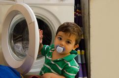 One and the half years old baby boy putting clothes in washing machine. One and the half years old baby boy helping his mom by putting clothes in washing machine stock photo