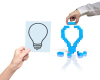 One hand building stack blocks lightbulb the other holding bluep Stock Photos