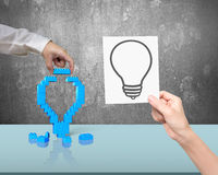 One hand building stack blocks lightbulb the other holding bluep Stock Photography
