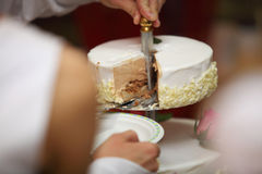 One hand cutting beautiful wedding cake Stock Image