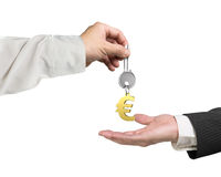 One hand giving key Euro sign keyring to another hand Royalty Free Stock Photos