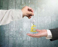 One hand giving key pound symbol keyring to another hand Royalty Free Stock Photo