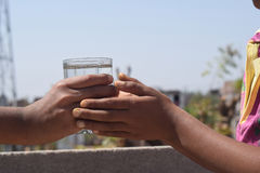 One hand giving water to a thirsty person. Stock Images