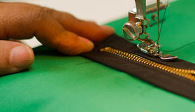 One hand holding a dark zipper, sewing machine making the job on a green fabric.  Royalty Free Stock Photography