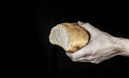 One hand holding a loaf of bread isolated on black. One male hand holding a loaf of bread isolated on a black background stock image