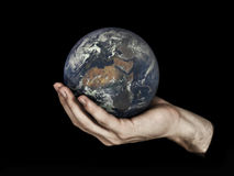 One hand holding planet Earth isolated on black. Elements of this image furnished by NASA. One male hand holding planet Earth isolated on a black background royalty free stock images
