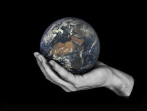 One hand holding planet Earth isolated on black.   Stock Image