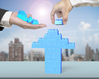One hand holding stack blocks the other completing arrow up Stock Photo