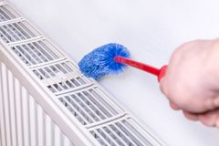 Cleaning a radiator with a brush royalty free stock images