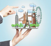 One hand holds a tablet with drawn hologram touristic places, another hand points out the most beautiful touristic places. The con Royalty Free Stock Image