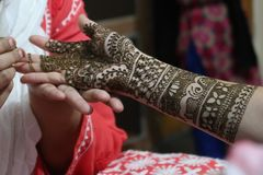 One hand of indian bride with henna mehndi in process Royalty Free Stock Photo