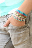 One Hand In My Pocket. Hand of girl with four handmade bracelet Royalty Free Stock Images
