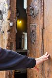 One hand is opening an old door royalty free stock image