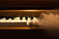 One Hand Playing The Piano. One hand in blur-motion playing the piano Stock Photos