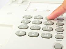 One hand pressing key on phone Stock Image