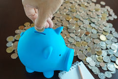 One hand putting coin into piggy bank Royalty Free Stock Photo