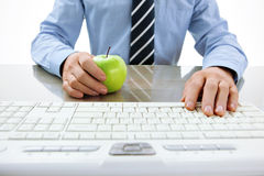 One hand typing text on keyboard and the other hand holding an apple. Healthy snacking concept Stock Photo