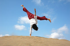 One handed holiday cartwheel. Girl doing a one handed cartwheel whilst on holiday in Gran Canaria royalty free stock images
