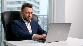 Businessman in formal wear using laptop in office. One handsome male person in formal wear sit in workspace at table and use computer, writing concept and ideas stock video footage