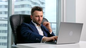 Businessman in formal wear using laptop in office. One handsome male person in formal wear sit in workspace at table and use computer, writing concept and ideas stock footage