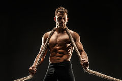 One handsome sexual strong young man with muscular body holding rope Royalty Free Stock Photography