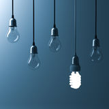 One hanging energy saving light bulb glowing different stand out from unlit incandescent bulbs Stock Photos