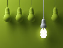 One hanging energy saving light bulb glowing different stand out from unlit incandescent lightbulbs Stock Image