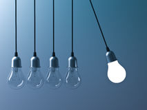 One hanging light bulb glowing different and stand out from unlit incandescent bulbs like newtons cradle on dark cyan Stock Photos