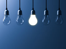 One hanging light bulb glowing different and standing out from unlit incandescent bulbs with reflection on dark blue background Royalty Free Stock Images