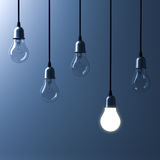 One hanging light bulb glowing different and standing out from unlit incandescent bulbs. With reflection on dark blue background , leadership and different Royalty Free Stock Image