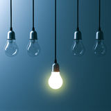 One hanging light bulb glowing different and standing out from unlit incandescent bulbs Stock Image